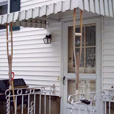 crutches holding up awning in front of house