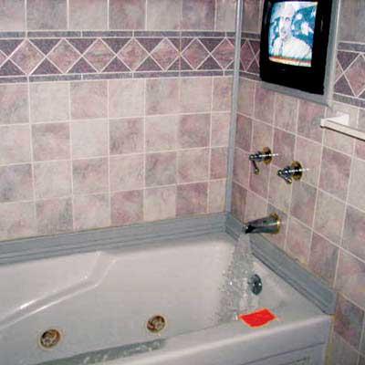 television set behind shower in bathtub