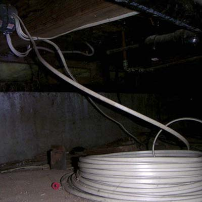 an entire roll of electrical wire hooked up at a crawlspace junction box