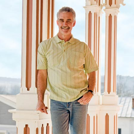 homeowner Vic Young leaning against a porch column of his restored Italianate house