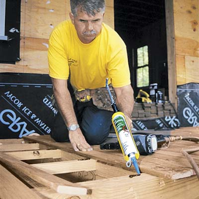 Tom Silva lays boards for a new deck.