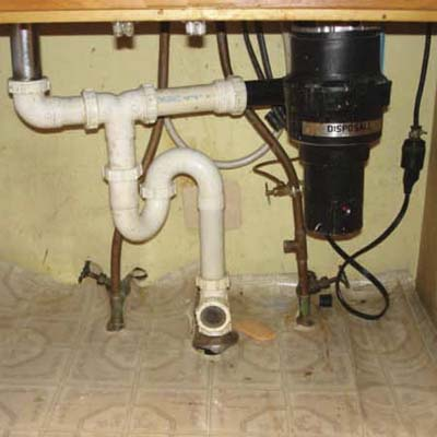 mayhem under a sink including an exposed extension cord, an innapropriate s trap and a clear glass drain line