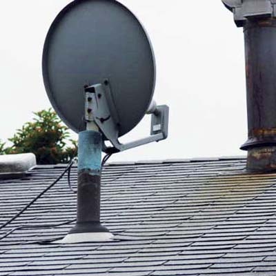 satellite dish mounted inside a plumbing vent pipe on the roof of a house
