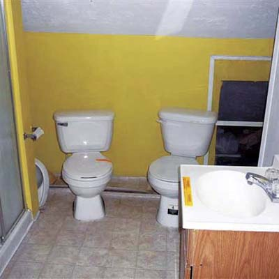 two working toilets installed next to each other in an open bathroom, with no plumbing vent