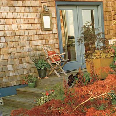 wood deck attached to shingled house featuring container gardens with foliage and colorful plants