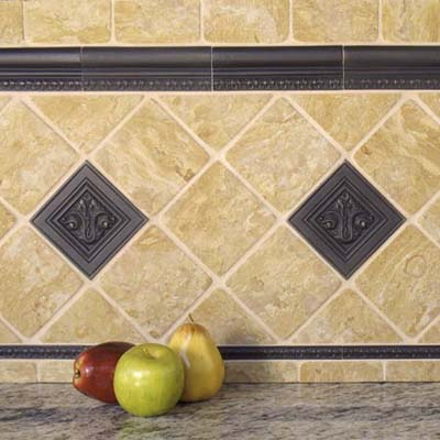 bronze tiles made by Saint-Gaudens used in a backsplash with fruit in the foreground