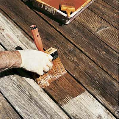 hand using brush to re-seal weather-beaten deck boards