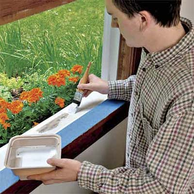 man reaching through window to paint exterior window sill