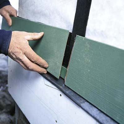 hands replacing damaged clapboard on house exterior