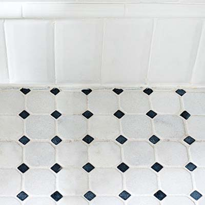 creative use of subway tile makes a baseboard for this classic twenties style remodeled bath