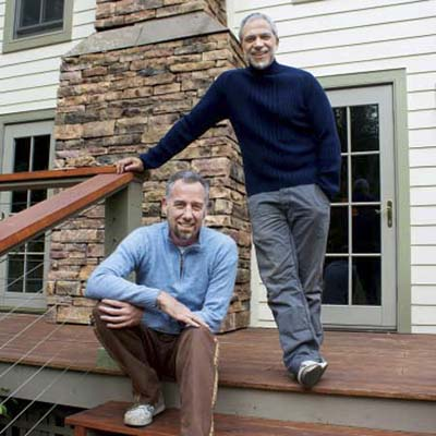 homeowners on the side stairs of their newly remodeled farmhouse