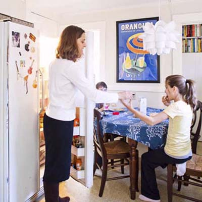 homeowner standing before her open refrigerator demonstrating how tight a fit the current kitchen configuration is
