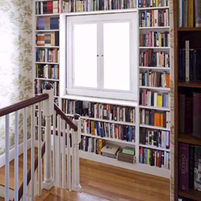 current landing before remodel with bookshelves framing the second-floor landing window