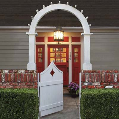 entryway with red-painted door and white archway