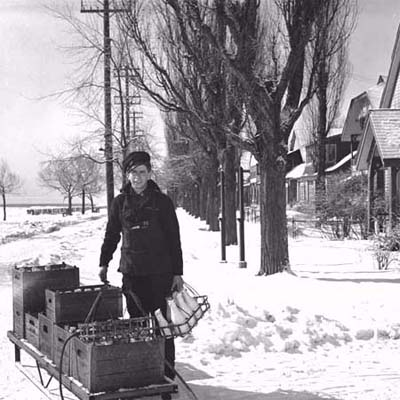 milkman with milk cart making deliveries on a snowy residential street
