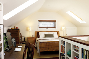 attic bedroom with built-in shelves and skylights