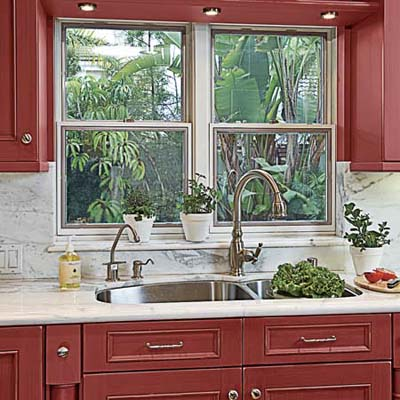 sink with marble countertops, backsplash, and behind-the-sink windowsill