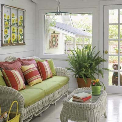 green couch with striped throw pillows in sunroom in remodeled 1909 Craftsman