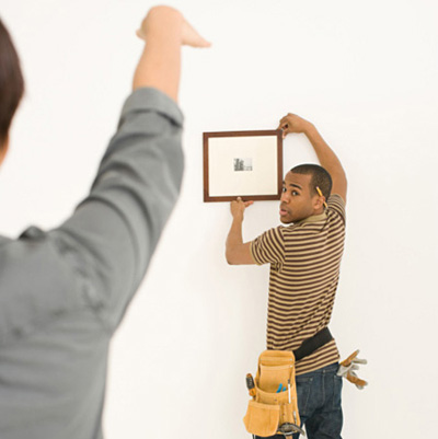 woman telling contractor where to hang frame