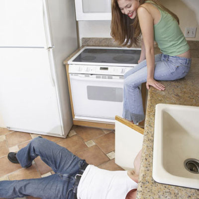 woman watching contractor working under sink