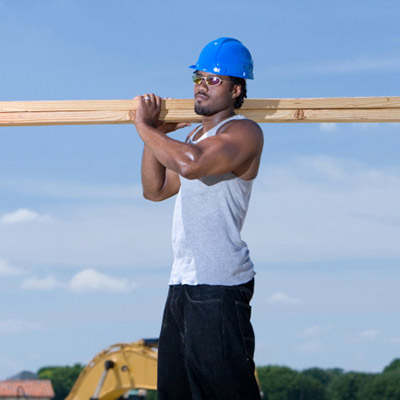 contractor with big muscles lifting wood planks