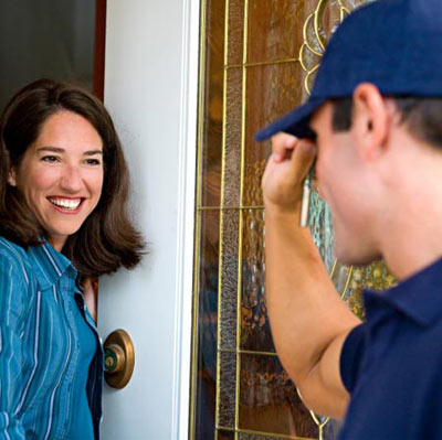 smiling woman greeting contractor at front door