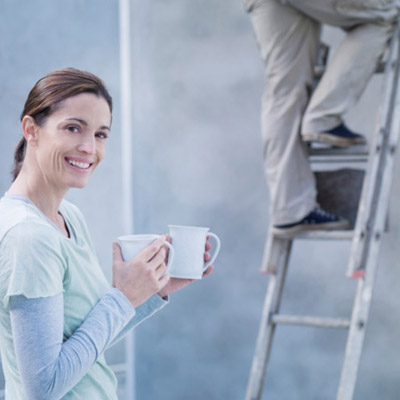woman holding two cups of coffee as man comes down ladder