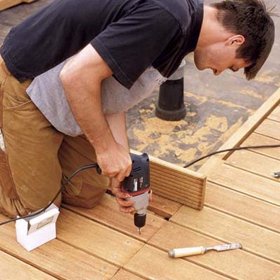 man installing composite decking