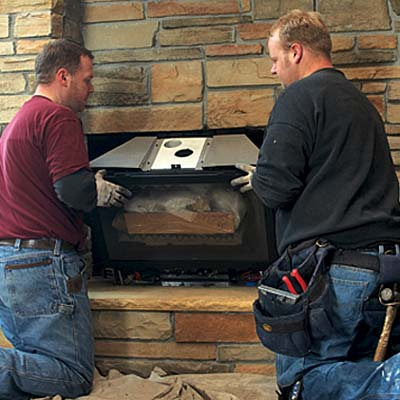 two men installing a gas-fireplace