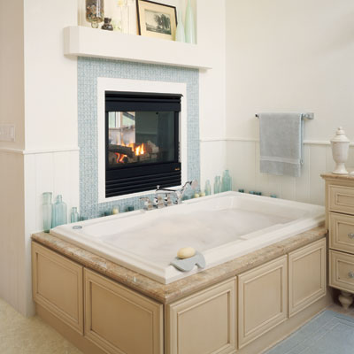 a gas fireplace over a large bathtub