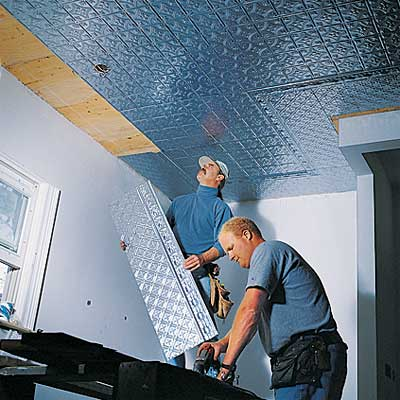 two people installing panels for the tin ceiling
