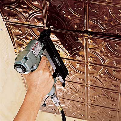 person using a pneumatic nailer to hang tin ceiling tiles
