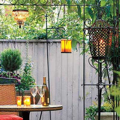 candles and lanterns at different heights in outdoor dining space