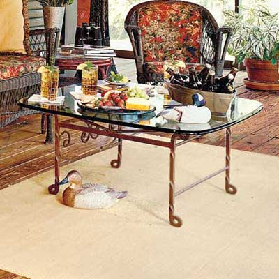 rusted iron and glass table and sisal rug on porch