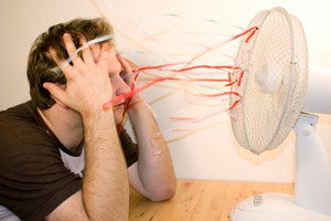 man cooling down in front of oscillating fan