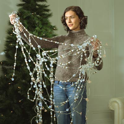 woman untangling christmas decorations in front of tree