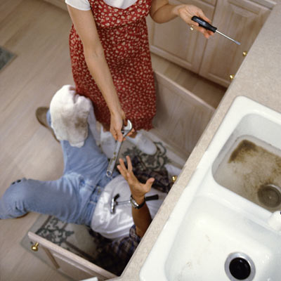 man fixing kitchen sink plumbing