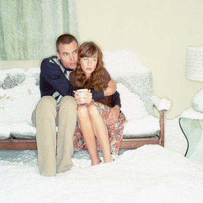 couple sitting in living room of snow