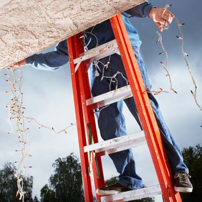 man on ladder hanging christmas lights on house exterior