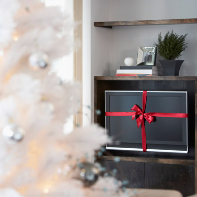 tv with red ribbon next to christmas tree