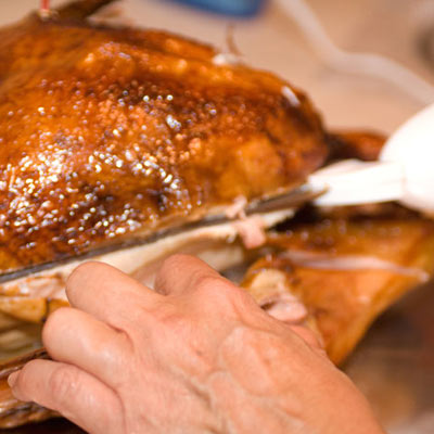 man cutting turkey with an electric knife