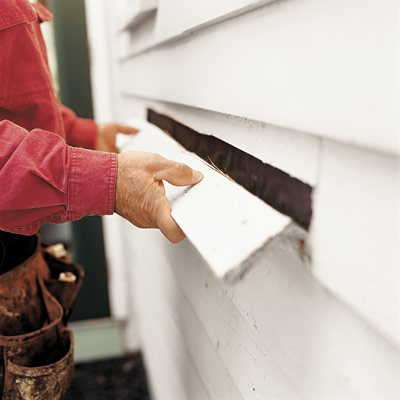 man removing damaged clapboard from house exterior