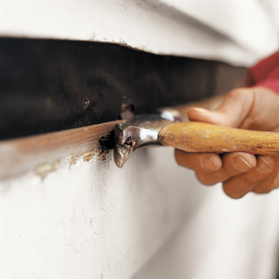 man removing bottom nails of clapboard siding