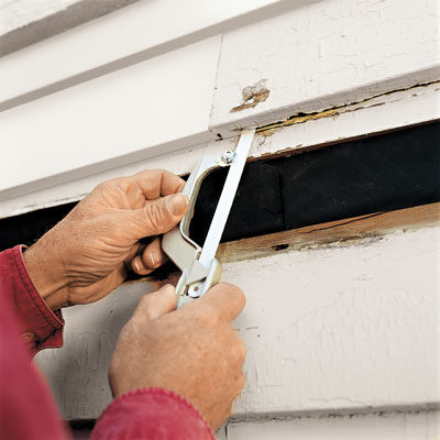 man using hacksaw blad to cut nails in clapboard siding