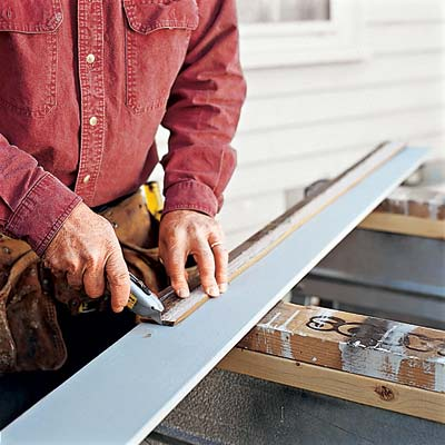 man marking and cutting replacement clapboard for exterior house siding