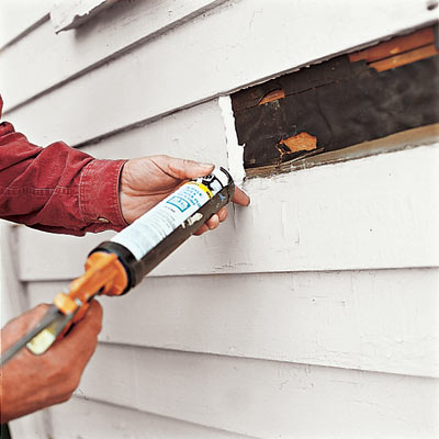 man caulking house exterior for replacement clapboard