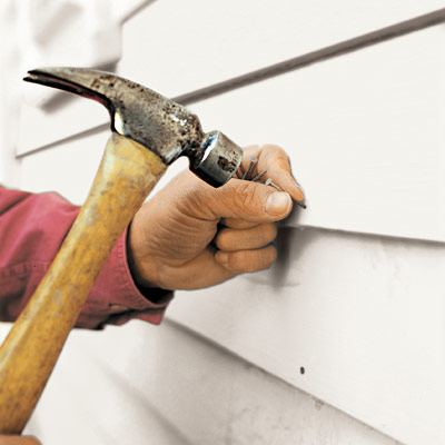 man fastening replacement clapboard to house exterior