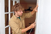 person installing weather stripping to a door