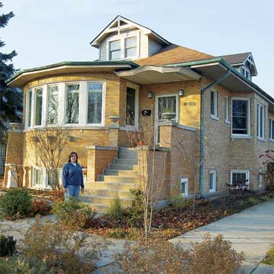 woman standing in front of her brick craftsman home in this chicago illinois best old house neighborhood
