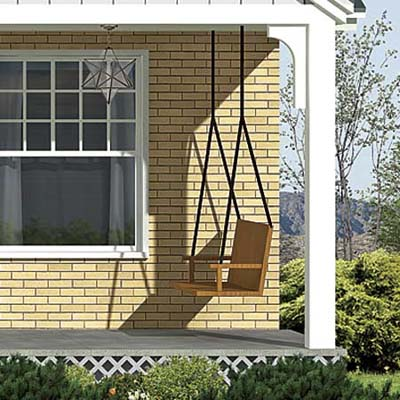 a porch swing is added in the photoshop redesign of this ranch style house